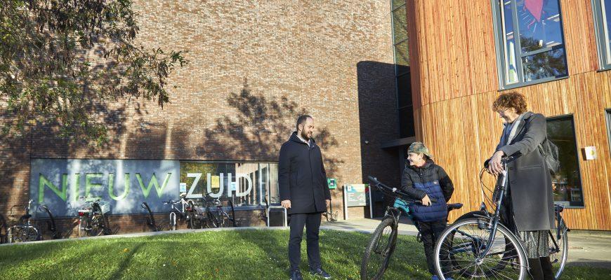 Wethouder Ufuk Kâhya samen met eerste leerling Gijs Heerkens en projectleider Angelie Ackermans bij de ingang van de school.